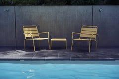 Las sillas y la tabla amarillas en la piscina echan a un lado foto de archivo libre de regalías