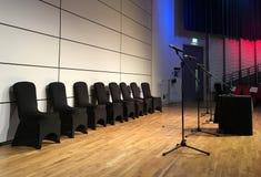 Las sillas y los micrófonos negros pusieron listo para la presentación en auditorio foto de archivo