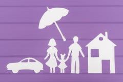 Las siluetas cortaron del papel del hombre y de la mujer con una muchacha debajo del paraguas, de la casa y del coche cerca fotos de archivo libres de regalías