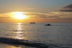 Las siluetas de dos barcos acercan a la isla del batanta en la puesta del sol Foto de archivo
