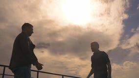 Las siluetas de dos hombres sacuden las manos Apretón de manos apretón de manos en el fondo del cielo y de la puesta del sol Cáma almacen de video
