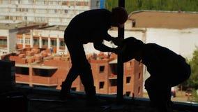 Las siluetas de dos trabajadores que sueldan con autógena un metal emiten metrajes