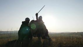 Las siluetas de guerreros de Vikingos están luchando durante ataque Contre-jour metrajes