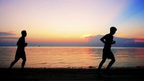 Las siluetas de hombres jovenes están corriendo en la playa tropical en la puesta del sol que sorprende Cámara lenta 1920x1080 almacen de metraje de vídeo