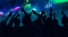 Las siluetas de la gente del baile delante de la etapa brillante se encienden Foto de archivo