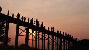 Las siluetas de la gente del puente de U Bein en la puesta del sol alisan el sonido del tiro w del carro almacen de metraje de vídeo