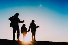 Las siluetas de la madre con los niños gozan el caminar en la puesta del sol Fotografía de archivo
