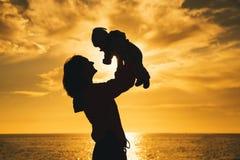 Las siluetas de la madre y del bebé en la puesta del sol en el mar varan Imágenes de archivo libres de regalías