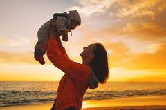 Las siluetas de la madre y del bebé en la puesta del sol en el mar varan Imagen de archivo libre de regalías