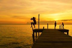 Las siluetas de la mujer saltan en el mar del embarcadero Fotos de archivo