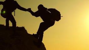 Las siluetas de los escaladores estiran sus manos el uno al otro, subiendo al top de la colina Trabajo en equipo de hombres de ne almacen de metraje de vídeo