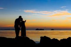 Las siluetas de los pares en la playa imagenes de archivo