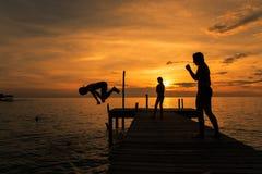 Las siluetas de niños saltan en el mar del embarcadero Imagen de archivo
