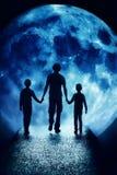 Las siluetas de niños y del adulto están antes de la luna Imágenes de archivo libres de regalías