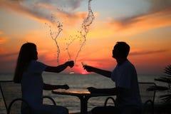Las siluetas de pares salpican hacia fuera la bebida del vidrio Foto de archivo