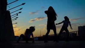 Las siluetas de tres muchachas de los bailarines de ballet moderno son de mudanza y girantes en una calle en el fondo del cielo d metrajes
