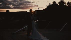 Las siluetas de un par cariñoso del casar abrazan nuevamente y los besos en la puesta del sol almacen de video