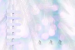 Las siluetas del ciclista en la flecha de madera del color violeta señalizan en verde borroso del rosa de las luces suavemente Imágenes de archivo libres de regalías