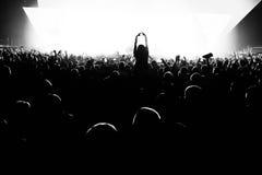 Las siluetas del concierto aprietan delante de luces brillantes de la etapa con confeti Fotografía de archivo libre de regalías