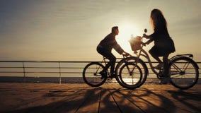 Las siluetas del montar a caballo joven de los pares montan en bicicleta en el terraplén del mar y la conducción más allá de uno  metrajes