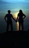 Las siluetas representan el amor de pares con el contexto hermoso de la puesta del sol fotos de archivo libres de regalías