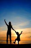 Las siluetas sirven de madre y niño en ocaso Fotografía de archivo libre de regalías
