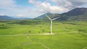 Las solas cuchillas de turbina de viento giran contra las montañas distantes almacen de metraje de vídeo