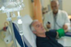 Las soluciones salinas embotellan la ejecución y el goteo en hospital fotos de archivo libres de regalías