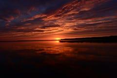 Las sombras y la puesta del sol se encienden en la superficie del agua del lago Foto de archivo