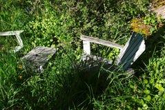 Las sombras y las malas hierbas ocultan dos sillas verdes del adirondack en el jardín fotos de archivo