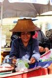Las sonrisas de los comerciantes que venden las mercancías a bordo Fotos de archivo