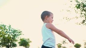 Las sonrisas del niño pequeño y dan vuelta alrededor Niñez feliz Retrato de un niño activo alegre almacen de metraje de vídeo