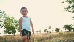 Las sonrisas del niño pequeño y dan vuelta alrededor Niñez feliz Retrato de un niño activo alegre almacen de video