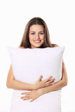 Las sonrisas hermosas de la muchacha y abrazan su almohada Foto de archivo