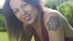 Las sonrisas hermosas de la mujer que mienten en hierba verde en parque, emoción de la cámara lenta gozan metrajes