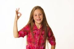 Las sonrisas hermosas jovenes de la niña que muestran la autorización de la mano firman encima whi Foto de archivo libre de regalías
