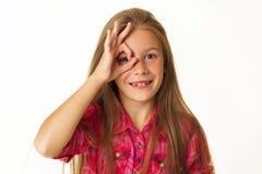 Las sonrisas hermosas jovenes de la niña que muestran la autorización de la mano firman encima whi Imágenes de archivo libres de regalías