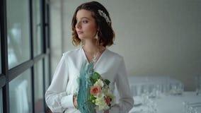 Las sonrisas morenas hermosas de la novia, en sus manos son un ramo de la flor Tiara hermosa en el pelo, maquillaje profesional almacen de metraje de vídeo