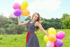 Las sonrisas rubias jovenes hermosas de la muchacha en un día de verano caminan con las bolas coloreadas en la ciudad Imagenes de archivo