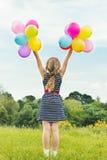 Las sonrisas rubias jovenes hermosas de la muchacha en un día de verano caminan con las bolas coloreadas en la ciudad Foto de archivo