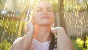 Las sonrisas y las risas de la mujer joven debajo de la lluvia Las gotas de lluvia caen en su cara y ella es feliz con vida y la  almacen de video