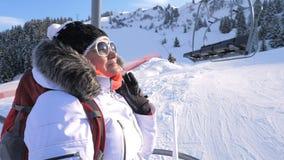 Las subidas del esquiador de la mujer una silla levantan para arriba una montaña en una estación de esquí fotos de archivo libres de regalías