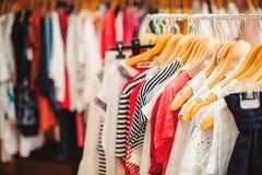 Las suspensiones de ropa con ropa colorida en las mujeres hacen compras Venta del verano Imagen de archivo