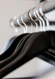 Las suspensiones negras colgaron en encuesta rústica debajo de estante en guardarropa imagen de archivo libre de regalías