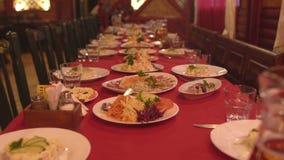 Las tablas preparadas fijaron en un restaurante para celebrar una celebración, un aperitivo almacen de metraje de vídeo