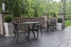 Las tablas y las sillas en patio por mañana se encienden imagen de archivo