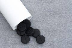 Las tabletas activadas del carbón de leña para limpiar el cuerpo desbordaron una botella en Gray Background Imagenes de archivo