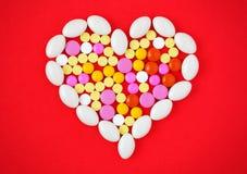 Las tabletas coloridas arreglaron en una forma del corazón en fondo rojo Imagen de archivo libre de regalías