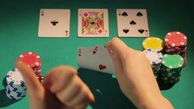 Las tarjetas de comprobación felices del jugador de póker, mostrando los pulgares-para arriba dan la muestra, juego afortunado almacen de video
