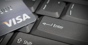 Las tarjetas de crédito en el botón del foco del teclado de ordenador entran con VISA Imagen de archivo libre de regalías